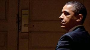 Obama somber looking over shoulder
